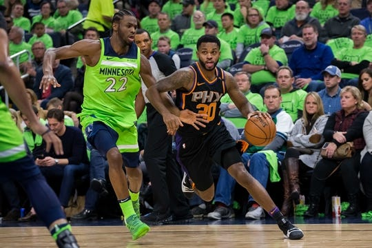 Dec 16, 2017; Minneapolis, MN, USA; Phoenix Suns guard Troy Daniels (30) dribbles in the third quarter against the Minnesota Timberwolves guard Andrew Wiggins (22) at Target Center. Mandatory Credit: Brad Rempel-USA TODAY Sports