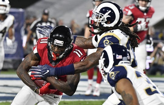 Jan 6, 2018; Los Angeles, CA, USA; Los Angeles Rams inside linebacker Mark Barron (26) tackles Atlanta Falcons wide receiver Julio Jones (11) in the first quarter in the NFC Wild Card playoff football game at Los Angeles Memorial Coliseum. Mandatory Credit: Robert Hanashiro-USA TODAY Sports