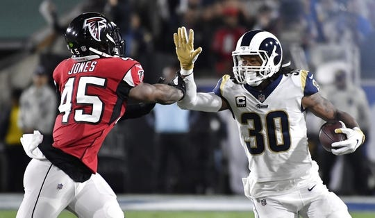 Jan 6, 2018; Los Angeles, CA, USA; Los Angeles Rams running back Todd Gurley (30) runs against Atlanta Falcons defensive back Leon McFadden (35) in the first quarter in the NFC Wild Card playoff football game at Los Angeles Memorial Coliseum. Mandatory Credit: Robert Hanashiro-USA TODAY Sports