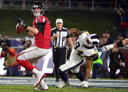 January 6, 2018; Los Angeles, CA, USA; Atlanta Falcons quarterback Matt Ryan (2) rolls out to pass under pressure from Los Angeles Rams outside linebacker Robert Quinn (94) during the first half in the NFC Wild Card playoff football game at the Los Angeles Memorial Coliseum. Mandatory Credit: Gary A. Vasquez-USA TODAY Sports