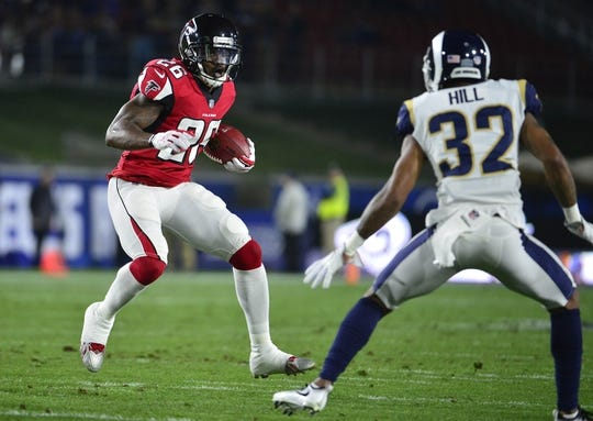 January 6, 2018; Los Angeles, CA, USA; Atlanta Falcons running back Tevin Coleman (26) runs the ball against Los Angeles Rams cornerback Troy Hill (32) during the first half in the NFC Wild Card playoff football game at the Los Angeles Memorial Coliseum. Mandatory Credit: Gary A. Vasquez-USA TODAY Sports