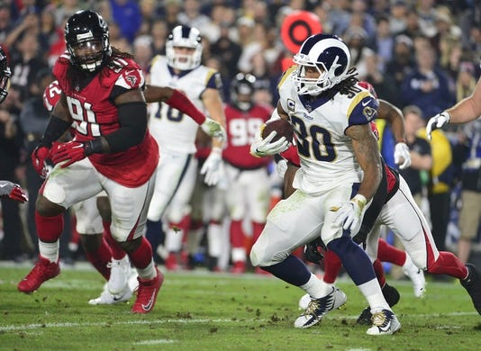 January 6, 2018; Los Angeles, CA, USA; Los Angeles Rams running back Todd Gurley (30) runs the all against Atlanta Falcons defensive end Courtney Upshaw (91) during the first half in the NFC Wild Card playoff football game at the Los Angeles Memorial Coliseum. Mandatory Credit: Gary A. Vasquez-USA TODAY Sports