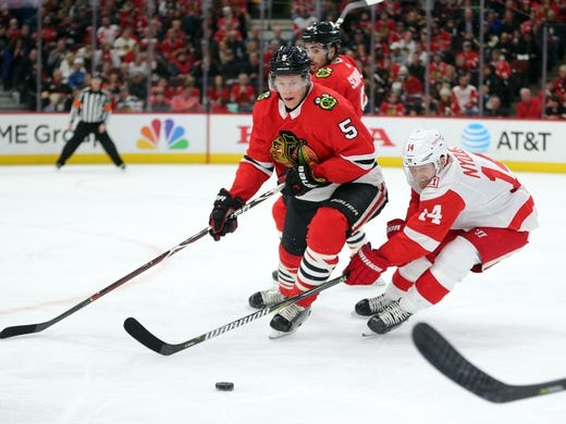 Jan 14, 2018; Chicago, IL, USA; Chicago Blackhawks defenseman Connor Murphy (5) and Detroit Red Wings center Gustav Nyquist (14) chase the puck during the second period at the United Center. Mandatory Credit: Dennis Wierzbicki-USA TODAY Sports