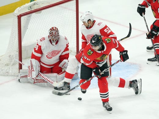 Jan 14, 2018; Chicago, IL, USA; Chicago Blackhawks right wing Ryan Hartman (38) tips a shot on Detroit Red Wings goalie Petr Mrazek (34) with defenseman Jonathan Ericsson (52) defending during the third period at the United Center. Detroit won 4-0. Mandatory Credit: Dennis Wierzbicki-USA TODAY Sports