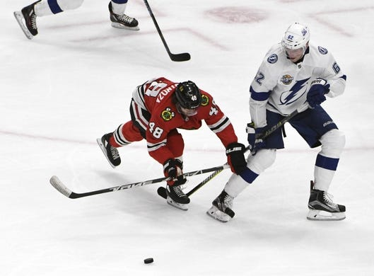 Jan 22, 2018; Chicago, IL, USA; Chicago Blackhawks left wing Vinnie Hinostroza (48) and Tampa Bay Lightning defenseman Andrej Sustr (62) chase the puck during the second period at United Center. Mandatory Credit: David Banks-USA TODAY Sports