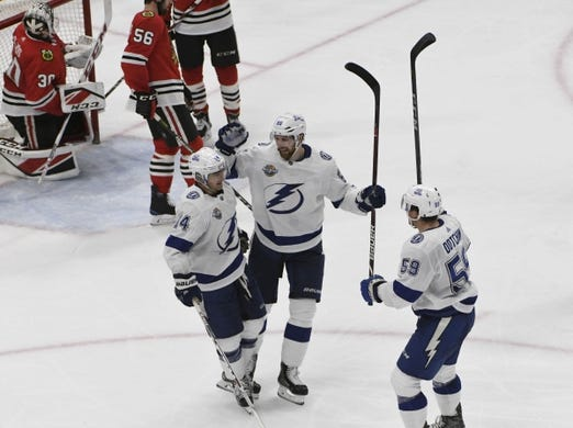 Jan 22, 2018; Chicago, IL, USA; Tampa Bay Lightning left wing Chris Kunitz (14) celebrates  with defenseman Braydon Coburn (55) and Jake Dotchin (59) after scoring a goal against the Chicago Blackhawks during the second period at United Center. Mandatory Credit: David Banks-USA TODAY Sports