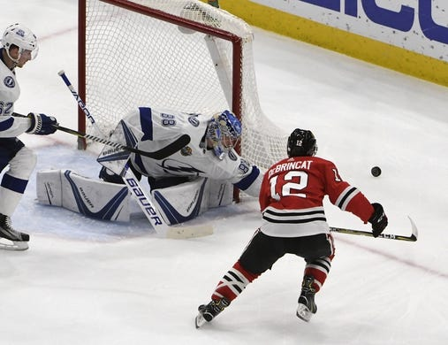 Jan 22, 2018; Chicago, IL, USA; Tampa Bay Lightning goaltender Andrei Vasilevskiy (88) swats the puck on a shot by Chicago Blackhawks right wing Alex DeBrincat (12) during the second period at United Center. Mandatory Credit: David Banks-USA TODAY Sports