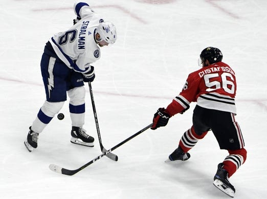 Jan 22, 2018; Chicago, IL, USA;  Chicago Blackhawks defenseman Erik Gustafsson (56) and Tampa Bay Lightning defenseman Anton Stralman (6) go for the puck during the third period at United Center. Mandatory Credit: David Banks-USA TODAY Sports