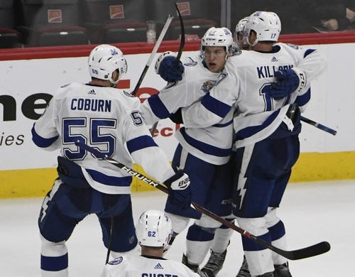 Jan 22, 2018; Chicago, IL, USA; Tampa Bay Lightning center Yanni Gourde (center) reacts after scoring a goal against the Chicago Blackhawks during the third period at United Center. Mandatory Credit: David Banks-USA TODAY Sports