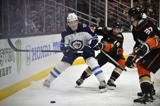 January 25, 2018; Anaheim, CA, USA; Winnipeg Jets defenseman Jacob Trouba (8) plays the puck against Anaheim Ducks center Adam Henrique (14) and left wing Nick Ritchie (37) during the first period at Honda Center. Mandatory Credit: Gary A. Vasquez-USA TODAY Sports