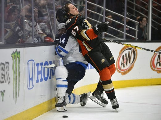 January 25, 2018; Anaheim, CA, USA; Anaheim Ducks center Rickard Rakell (67) hits Winnipeg Jets defenseman Josh Morrissey (44) against the boards while playing for the puck during the first period at Honda Center. Mandatory Credit: Gary A. Vasquez-USA TODAY Sports