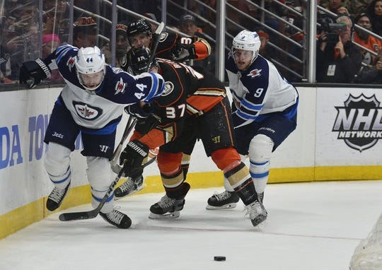 January 25, 2018; Anaheim, CA, USA; Winnipeg Jets defenseman Josh Morrissey (44) and center Andrew Copp (9) play for the puck against Anaheim Ducks left wing Nick Ritchie (37) and right wing Jakob Silfverberg (33) during the first period at Honda Center. Mandatory Credit: Gary A. Vasquez-USA TODAY Sports