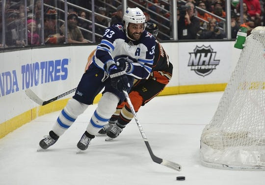 January 25, 2018; Anaheim, CA, USA; Winnipeg Jets defenseman Dustin Byfuglien (33) moves the puck against the Anaheim Ducks during the first period at Honda Center. Mandatory Credit: Gary A. Vasquez-USA TODAY Sports