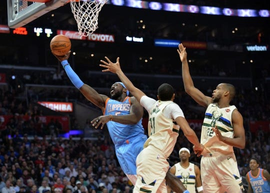 March 27, 2018; Los Angeles, CA, USA; Los Angeles Clippers forward Montrezl Harrell (5) moves to the basket against Milwaukee Bucks center John Henson (31) and forward Khris Middleton (22) during the first half at Staples Center. Mandatory Credit: Gary A. Vasquez-USA TODAY Sports