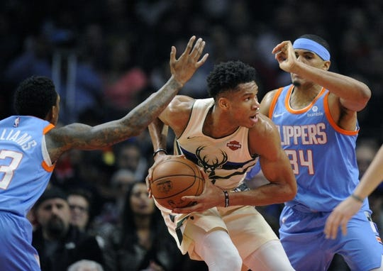 March 27, 2018; Los Angeles, CA, USA; Milwaukee Bucks forward Giannis Antetokounmpo (34) moves the ball against Los Angeles Clippers forward Tobias Harris (34) and guard Lou Williams (23) during the first half at Staples Center. Mandatory Credit: Gary A. Vasquez-USA TODAY Sports