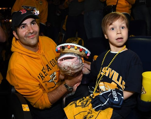 May 5, 2018; Nashville, TN, USA; Nashville Predators fan Tom Dennis poses with Caleb Daniel, a heart transplant patient from Vanderbilt Children's Hospital, and a catfish Daniel wanted to throw on the ice before game five of the second round of the 2018 Stanley Cup Playoffs between the Nashville Predators and Winnipeg Jets at Bridgestone Arena. Mandatory Credit: Christopher Hanewinckel-USA TODAY Sports
