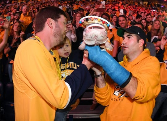 May 5, 2018; Nashville, TN, USA; Nashville Predators fan Zack Daniel (left) and Tom Dennis help Caleb Daniel, a heart transplant patient from Vanderbilt Children's Hospital, throw a catfish on the ice before game five of the second round of the 2018 Stanley Cup Playoffs between the Nashville Predators and Winnipeg Jets at Bridgestone Arena. Mandatory Credit: Christopher Hanewinckel-USA TODAY Sports