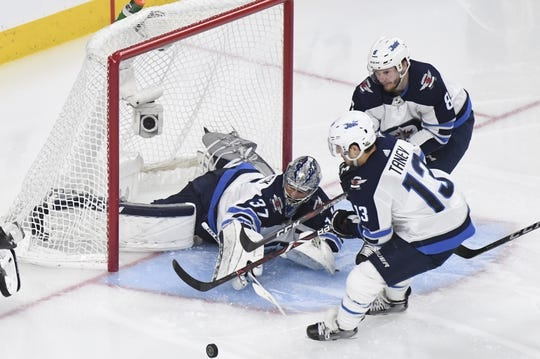 May 16, 2018; Las Vegas, NV, USA; Winnipeg Jets goalie Connor Hellebuyck (37) attempts to block the puck in front of left wing Brandon Tanev (13) during the second period in game three of the Western Conference Final of the 2018 Stanley Cup Playoffs against the Winnipeg Jets at T-Mobile Arena. Mandatory Credit: Kirby Lee-USA TODAY Sports