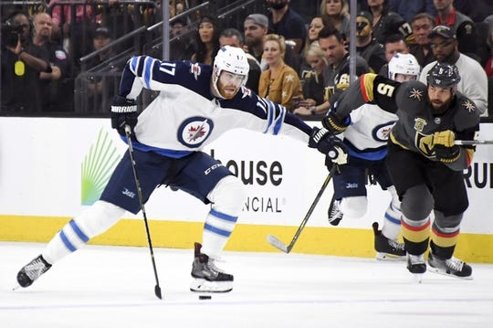 May 16, 2018; Las Vegas, NV, USA; Winnipeg Jets center Adam Lowry (17) moves the puck ahead of Vegas Golden Knights defenseman Deryk Engelland (5) during the first period in game three of the Western Conference Final of the 2018 Stanley Cup Playoffs at T-Mobile Arena. Mandatory Credit: Kirby Lee-USA TODAY Sports