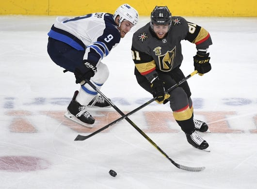 May 16, 2018; Las Vegas, NV, USA; Vegas Golden Knights center Jonathan Marchessault (81) moves the puck under pressure by Winnipeg Jets center Andrew Copp (9) during the first period in game three of the Western Conference Final of the 2018 Stanley Cup Playoffs at T-Mobile Arena. Mandatory Credit: Stephen R. Sylvanie-USA TODAY Sports