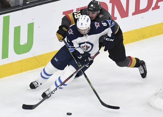 May 16, 2018; Las Vegas, NV, USA; Winnipeg Jets defenseman Jacob Trouba (8) moves the puck under pressure by Vegas Golden Knights right wing Reilly Smith (19) during the second period in game three of the Western Conference Final of the 2018 Stanley Cup Playoffs at T-Mobile Arena. Mandatory Credit: Kirby Lee-USA TODAY Sports