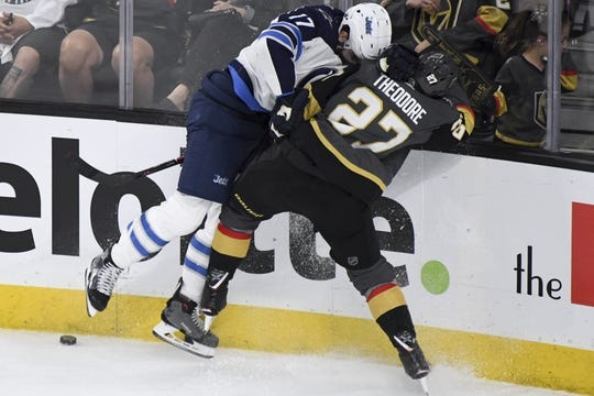 May 16, 2018; Las Vegas, NV, USA; Winnipeg Jets center Adam Lowry (17) and Vegas Golden Knights defenseman Shea Theodore (27) battle for the puck during the second period in game three of the Western Conference Final of the 2018 Stanley Cup Playoffs at T-Mobile Arena. Mandatory Credit: Kirby Lee-USA TODAY Sports