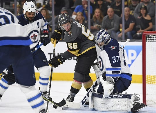 May 16, 2018; Las Vegas, NV, USA; Vegas Golden Knights left wing Erik Haula (56) attempts to deflect a shot in front of Winnipeg Jets goalie Connor Hellebuyck (37) in game three of the Western Conference Final of the 2018 Stanley Cup Playoffs at T-Mobile Arena. Mandatory Credit: Stephen R. Sylvanie-USA TODAY Sports