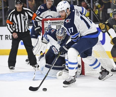 May 16, 2018; Las Vegas, NV, USA; Winnipeg Jets center Adam Lowry (17) moves the puck in game three of the Western Conference Final of the 2018 Stanley Cup Playoffs against the Vegas Golden Knights at T-Mobile Arena. Mandatory Credit: Stephen R. Sylvanie-USA TODAY Sports
