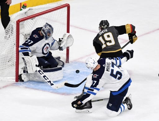 May 16, 2018; Las Vegas, NV, USA; Vegas Golden Knights right wing Reilly Smith (19) shoots the puck as Winnipeg Jets goaltender Connor Hellebuyck (37) and right wing Keegan Kolesar (55) defend  in the second period of game three of the Western Conference Final of the 2018 Stanley Cup Playoffs at T-Mobile Arena. Mandatory Credit: Kirby Lee-USA TODAY Sports