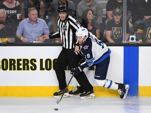 May 16, 2018; Las Vegas, NV, USA; Winnipeg Jets center Andrew Copp (9) gets caught up with NHL linesman Matt MacPherson during the first period against the Vegas Golden Knights in game three of the Western Conference Final of the 2018 Stanley Cup Playoffs at T-Mobile Arena. Mandatory Credit: Stephen R. Sylvanie-USA TODAY Sports