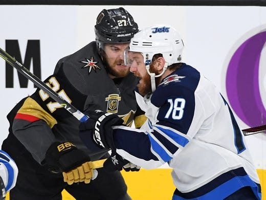 May 16, 2018; Las Vegas, NV, USA; Vegas Golden Knights defenseman Shea Theodore (27) looks to check Winnipeg Jets center Bryan Little (18) during the first period of game three of the Western Conference Final of the 2018 Stanley Cup Playoffs at T-Mobile Arena. Mandatory Credit: Stephen R. Sylvanie-USA TODAY Sports
