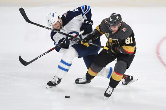 May 16, 2018; Las Vegas, NV, USA; Winnipeg Jets defenseman Jacob Trouba (8) lifts the stick of Vegas Golden Knights center Jonathan Marchessault (81) during the first period of game three of the Western Conference Final of the 2018 Stanley Cup Playoffs at T-Mobile Arena. Mandatory Credit: Stephen R. Sylvanie-USA TODAY Sports