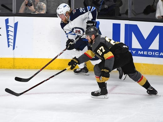 May 16, 2018; Las Vegas, NV, USA; Winnipeg Jets right wing Patrik Laine (29) skates along the boards as Vegas Golden Knights defenseman Shea Theodore (27) covers the play during the first period of game three of the Western Conference Final of the 2018 Stanley Cup Playoffs at T-Mobile Arena. Mandatory Credit: Stephen R. Sylvanie-USA TODAY Sports