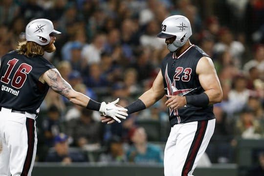 Jun 30, 2018; Seattle, WA, USA; Seattle Mariners designated hitter Nelson Cruz (23) is greeted by right fielder Ben Gamel (16) outside the dugout after scoring a run against the Kansas City Royals during the third inning at Safeco Field. Mandatory Credit: Joe Nicholson-USA TODAY Sports