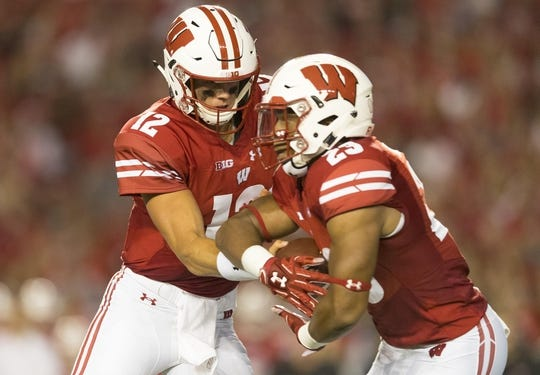 Aug 31, 2018; Madison, WI, USA; Wisconsin Badgers quarterback Alex Hornibrook (12) hands the football off to running back Jonathan Taylor (23) during the first quarter against the Western Kentucky Hilltoppers at Camp Randall Stadium. Mandatory Credit: Jeff Hanisch-USA TODAY Sports
