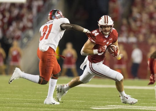 Aug 31, 2018; Madison, WI, USA; Wisconsin Badgers tight end Jake Ferguson (84) rushes with the football after catching a pass as Western Kentucky Hilltoppers defensive back Antwon Kincade (31) defends during the first quarter at Camp Randall Stadium. Mandatory Credit: Jeff Hanisch-USA TODAY Sports