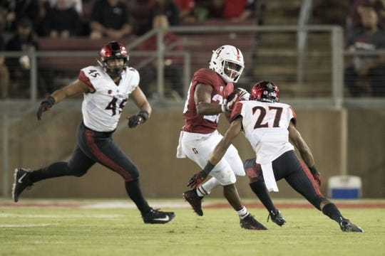 August 31, 2018; Stanford, CA, USA; Stanford Cardinal running back Bryce Love (20) runs against San Diego State Aztecs cornerback Kyree Woods (27) and defensive lineman Anthony Luke (45) during the third quarter at Stanford Stadium. Stanford defeated San Diego State 31-10. Mandatory Credit: Kyle Terada-USA TODAY Sports