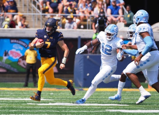 Sep 1, 2018; Berkeley, CA, USA; California Golden Bears quarterback Chase Garbers (7) elects to run ahead of North Carolina Tar Heels defensive end Tomon Fox (12) during the first quarter at California Memorial Stadium. Mandatory Credit: Kelley L Cox-USA TODAY Sports