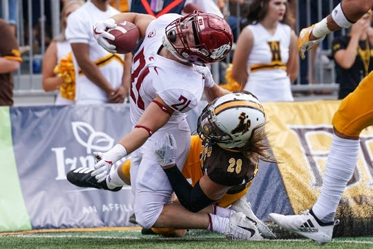 Sep 1, 2018; Laramie, WY, USA; Washington State Cougars running back Max Borghi (21) is horse collared by Wyoming Cowboys safety Andrew Wingard (28) during the first quarter at Jonah Field War Memorial Stadium. Mandatory Credit: Troy Babbitt-USA TODAY Sports