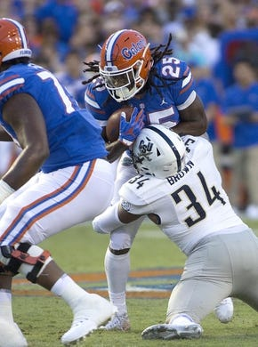 Sep 1, 2018; Gainesville, FL, USA; Florida Gators running back Jordan Scarlett (25) is tackled by Charleston Southern Buccaneers defensive end Solomon Brown (34) during the first quarter of play at Ben Hill Griffin Stadium. Mandatory Credit: Glenn Beil-USA TODAY Sports