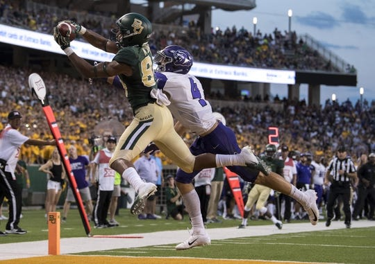 Sep 1, 2018; Waco, TX, USA; Baylor Bears wide receiver Marques Jones (84) catches a pass for a touchdown as Abilene Christian Wildcats safety Erik Huhn (4) defends during the first quarter at McLane Stadium. Mandatory Credit: Jerome Miron-USA TODAY Sports