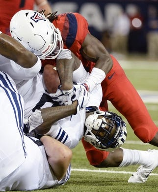 Sep 1, 2018; Tucson, AZ, USA; Brigham Young Cougars running back Squally Canada (22) is tackled by Arizona Wildcats safety Demetrius Flannigan-Fowles (6) during the first half at Arizona Stadium. Mandatory Credit: Casey Sapio-USA TODAY Sports