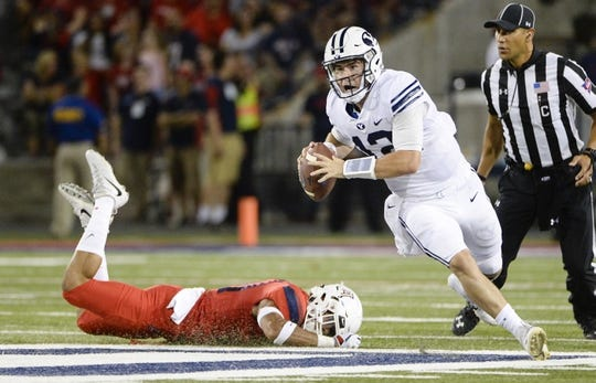 Sep 1, 2018; Tucson, AZ, USA; Brigham Young Cougars quarterback Tanner Mangum (12) escapes a tackle from Arizona Wildcats safety Tristan Cooper (31) during the first half at Arizona Stadium. Mandatory Credit: Casey Sapio-USA TODAY Sports