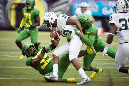 Sep 8, 2018; Eugene, OR, USA; Portland State Vikings quarterback Jalani Eason (10) is brought down by Oregon Ducks linebacker Kaulana Apelu (39) and linebacker Adrian Jackson (29) during the first half at Autzen Stadium. Mandatory Credit: Troy Wayrynen-USA TODAY Sports