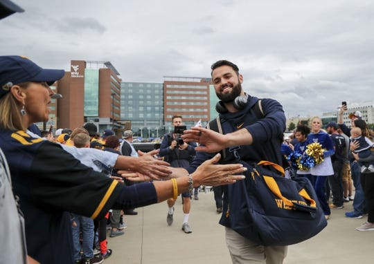 Sep 8, 2018; Morgantown, WV, USA; West Virginia Mountaineers quarterback Will Grier (right) arrives at the stadium before a game against the Youngstown State Penguins at Mountaineer Field at Milan Puskar Stadium. Mandatory Credit: Ben Queen-USA TODAY Sports