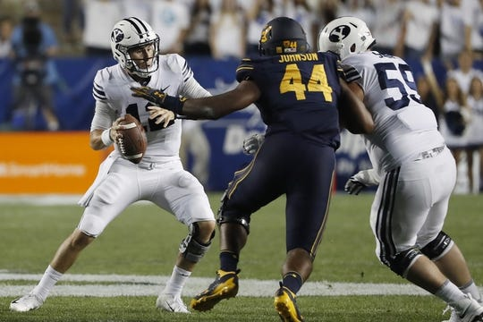 Sep 8, 2018; Provo, UT, USA; Brigham Young Cougars quarterback Tanner Mangum (12) can't avoid California Golden Bears defensive end Zeandae Johnson (44) in the second quarter at LaVell Edwards Stadium. Mandatory Credit: Jeff Swinger-USA TODAY Sports