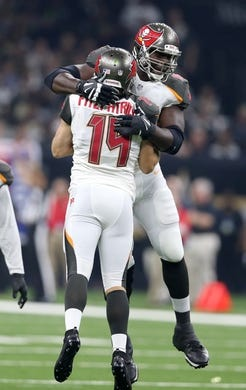 Sep 9, 2018; New Orleans, LA, USA; Tampa Bay Buccaneers offensive tackle Demar Dotson (69) celebrates a long touchdown pass with quarterback Ryan Fitzpatrick (14) in the first quarter against the New Orleans Saints at the Mercedes-Benz Superdome. Mandatory Credit: Chuck Cook-USA TODAY Sports