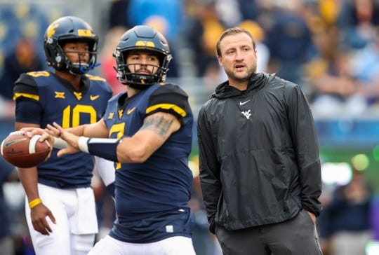 Sep 8, 2018; Morgantown, WV, USA; West Virginia Mountaineers offensive coordinator Jake Spavital talks with West Virginia Mountaineers quarterback Will Grier (7) prior to their game against the Youngstown State Penguins at Mountaineer Field at Milan Puskar Stadium. Mandatory Credit: Ben Queen-USA TODAY Sports