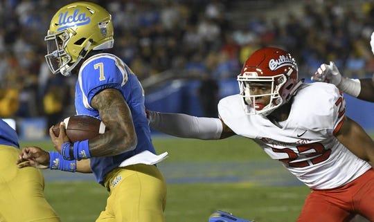 Sep 15, 2018; Pasadena, CA, USA; UCLA Bruins quarterback Dorian Thompson-Robinson (7) runs past Fresno State Bulldogs defensive back Juju Hughes (23) during the first quarter at the Rose Bowl. Mandatory Credit: Robert Hanashiro-USA TODAY Sports