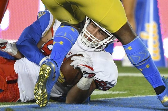 Sep 15, 2018; Pasadena, CA, USA; Fresno State Bulldogs tight end Kyle Riddering (89) drags a pair of UCLA defenders into the end zone to score a first quarter touchdown. Credit: Robert Hanashiro-USA TODAY Sports